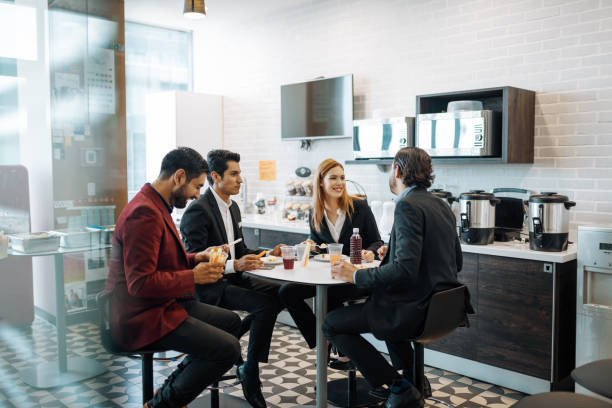 Millennial Latin coworkers taking a break at work, eating snack and chatting. stock photo