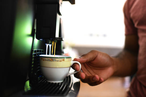 Millennial Male getting coffee from a bean to cup coffee machine stock photo