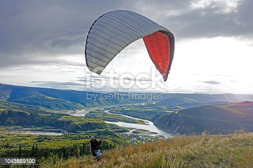 Young millennial male preparing para-glide for start from hill in Alaska close to Dawson City.