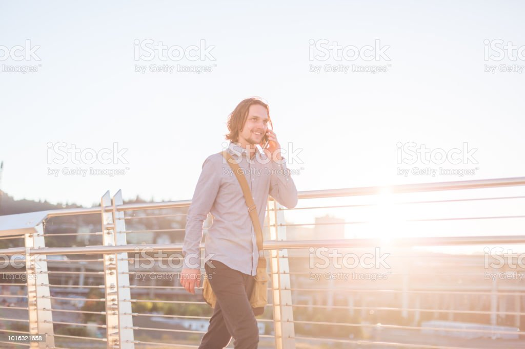 A young male in casual business clothes talks on his phone as he...