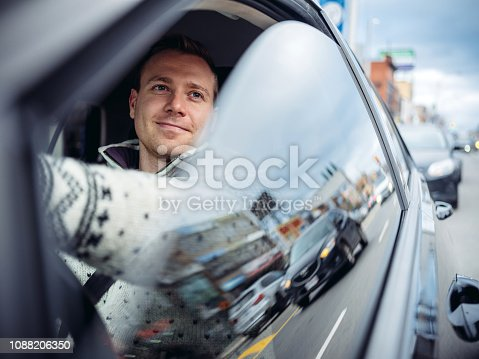 Caucasian Millennial man driving in a car in winter. Busy downtown street with people and cars in the background.