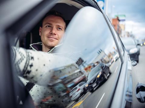 Millennial man driving in a car in winter