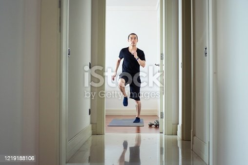 A mid adult man exercising at home.