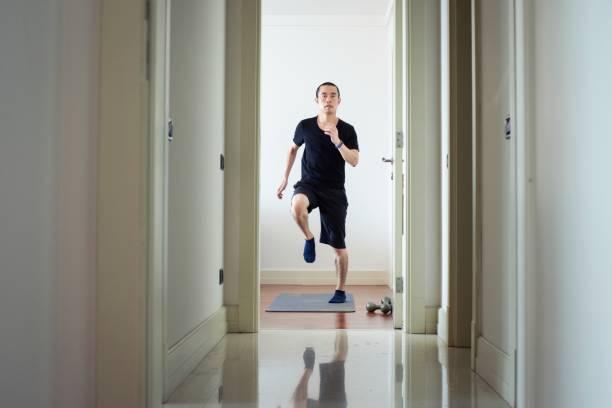 Millennial man exercising at home stock photo