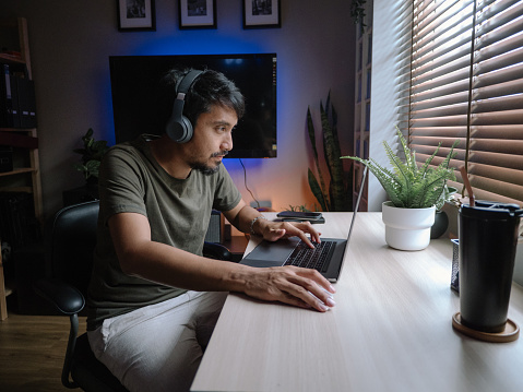Hipster asian man playing games on a laptop at home