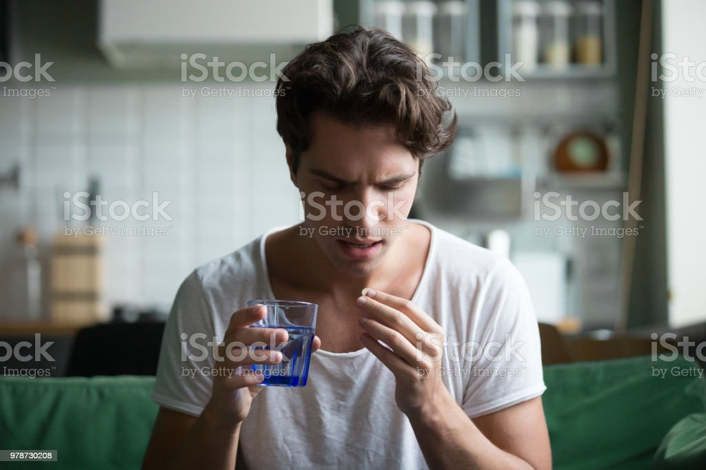 Millennial man taking pill to relieve pain at home Millennial man taking antibiotic antidepressant painkiller pill medication to relieve pain at home, young guy feeling sick ill suffering from headache, stress or flu, emergency treatment concept Accidents and Disasters Stock Photo