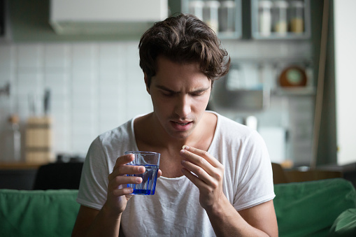 Millennial Man Taking Pill To Relieve Pain At Home Stock Photo - Download Image Now