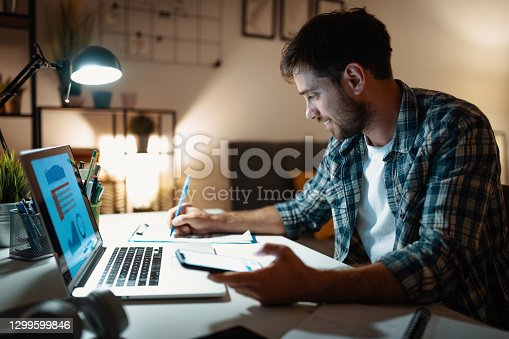 Millennial man working on laptop at home