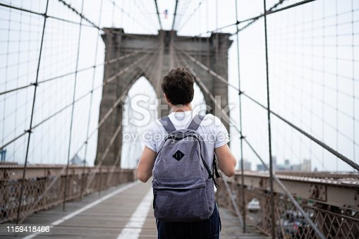 This is a color photograph of a young American man wearing a backpack as he walks across the Brooklyn Bridge in New York City, USA.