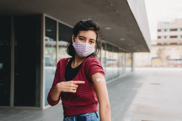 Millennial mixed race woman showing her arm where she just get vaccinated stock photo