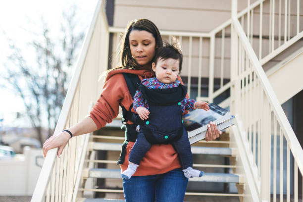 Millennial Mother College Student near Housing with Infant in Urban Environment stock photo
