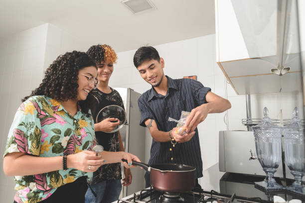 Millennial multi-ethnic flatmates cooking popcorn together stock photo