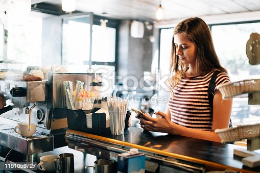 Millennial woman ordering at Coffee shop counter