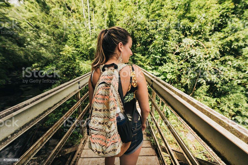 Millennial Woman Crossing Bridge Scenic Nature Travel Destination Hawaii stock photo