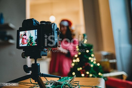 Millennial woman influencer recording a video of a tutorial: how to make the perfect gift box. She's at home, recording with a camera on a small tripod.