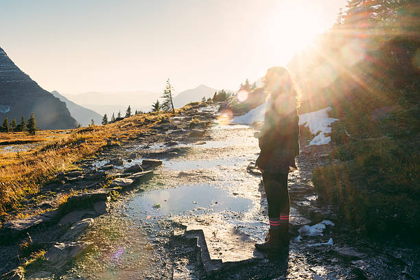 millennial woman on scenic hike in montana glacier national park - logan pass stock pictures, royalty-free photos & images