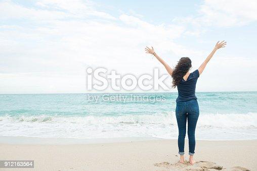 istock Millennial Woman Raising Arms at Beach Miami Florida Winter 912163564