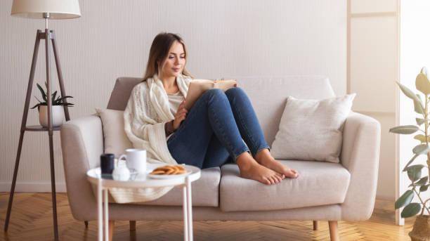 Millennial Frau lesen Buch zu Hause Interieur – Foto
