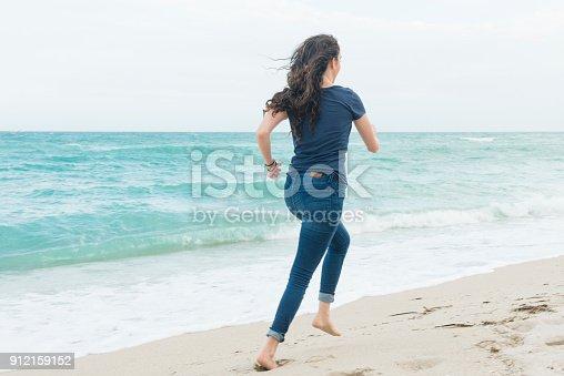 istock Millennial Woman Running Barefoot on Beach Miami Florida Winter 912159152