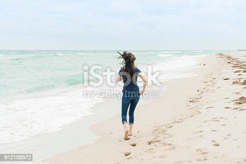 istock Millennial Woman Running Barefoot on Beach Miami Florida Winter 912159372