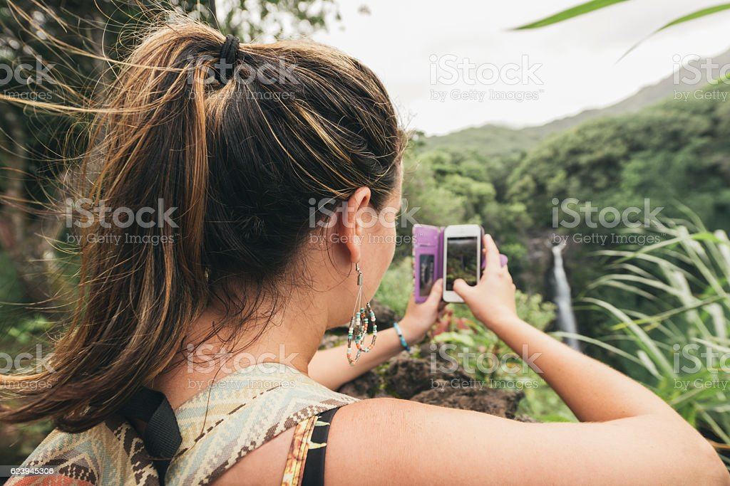 Millennial Woman Takes Pictures at Scenic Nature Travel Destination Hawaii stock photo