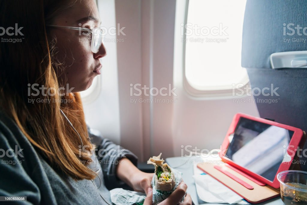 Millennial woman travelling alone in plane. stock photo