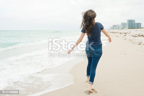 istock Millennial Woman Walking Barefoot on Beach Miami Florida Winter 912158688