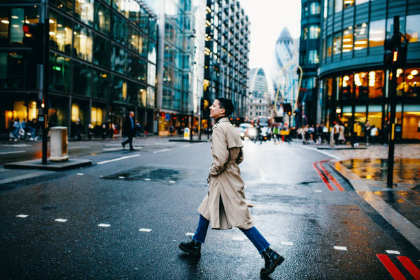 Millennial woman with short hair crossing the street on rainy day British lifestyle - living and commuting in London central london stock pictures, royalty-free photos & images