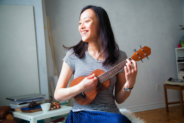 millennial young asian woman having fun playing ukulele in her studio apartment - music style stock pictures, royalty-free photos & images