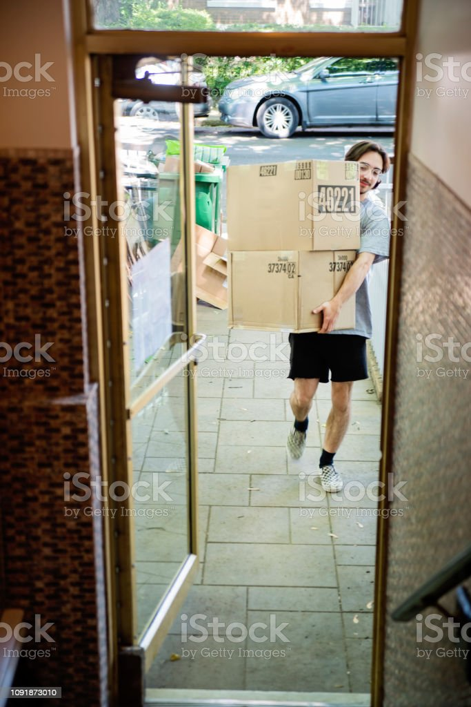 Millennial young man moving in new apartment. stock photo