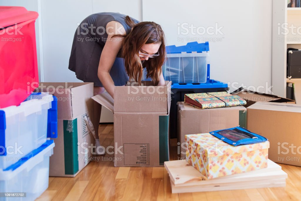 Millennial young woman moving in new apartment. stock photo