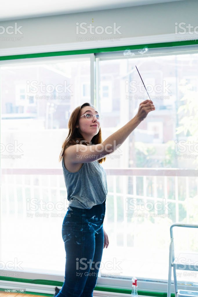 Millennial young woman purifying new apartment with incense. stock photo
