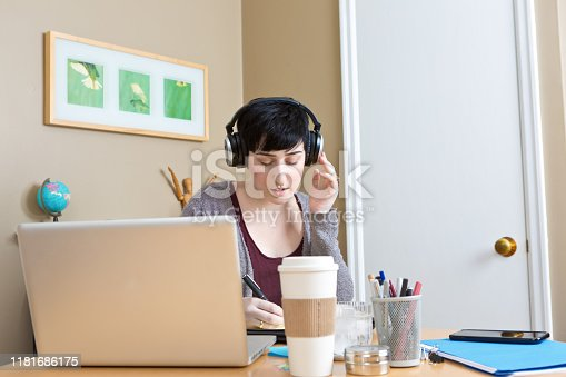 A Caucasian young woman millennial working in home office telecommuting using laptop computer, mobile devices doing business function. She is listening with a headphone.