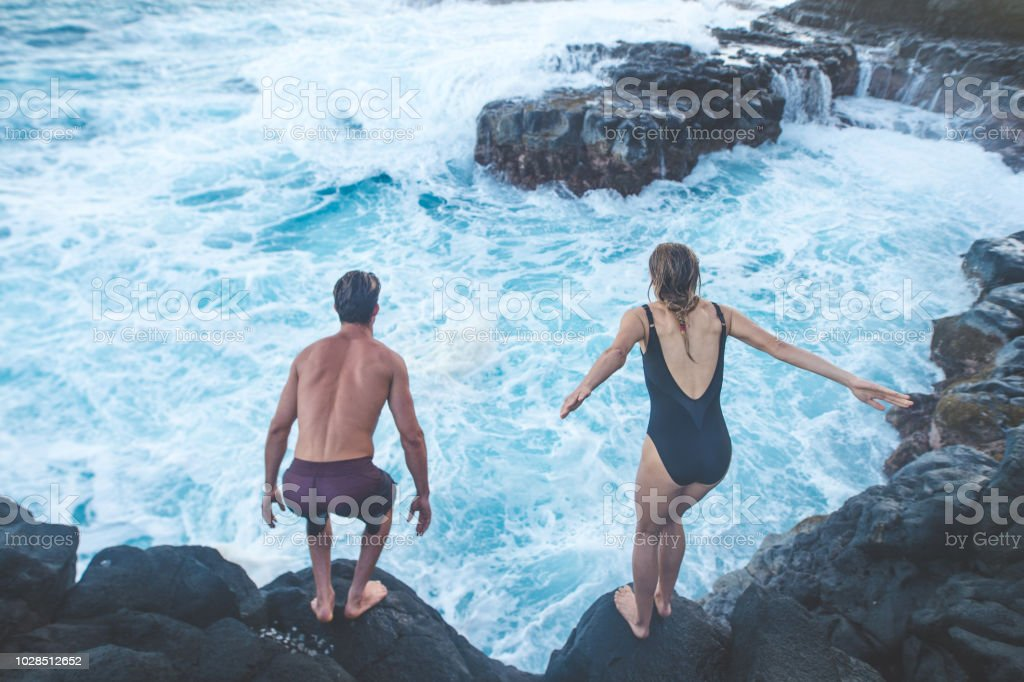 88e435dd6d2 A millennial-age couple getting ready to jump into the ocean - Stock image .