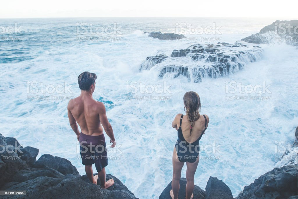 b7b3519697e A millennial-age couple getting ready to jump into the ocean royalty-free  stock