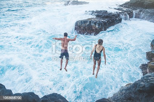 A millennial-age male and female jump from a rock cliff into the ocean. The waves are crashing into the rocks below and their arms are spread out. the shot is from behind them.