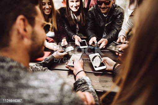 911294484istockphoto millennials at the cafe using the phone 1124646387
