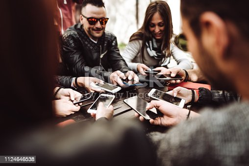 911294484istockphoto millennials at the cafe using the phone 1124646538