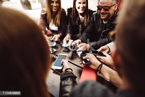 911294484istockphoto millennials at the cafe using the phone 1124646665