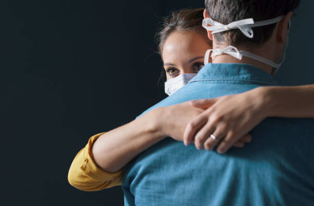 Millennials couple wearing a protective face mask and hugging stock photo