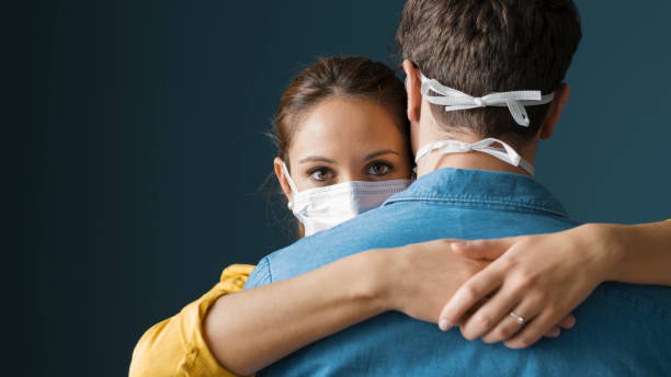 Millennials couple wearing a protective mask and hugging stock photo