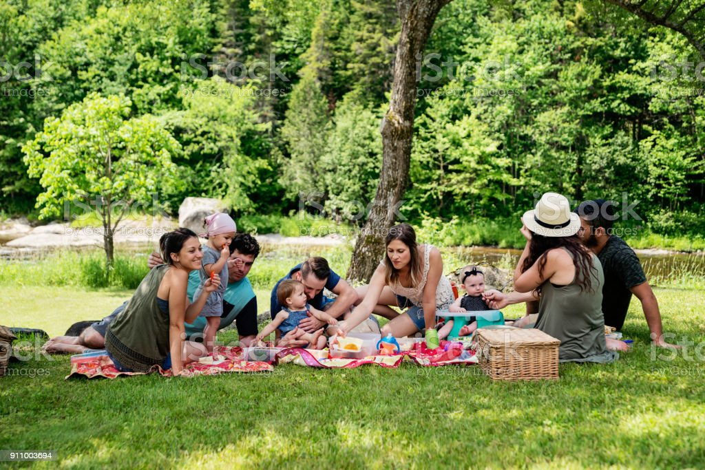 Millennials families having a picnic outdoors in summer. - Foto stock royalty-free di 18-23 mesi