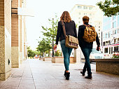 Two young millennials on a street in a modern urban area.