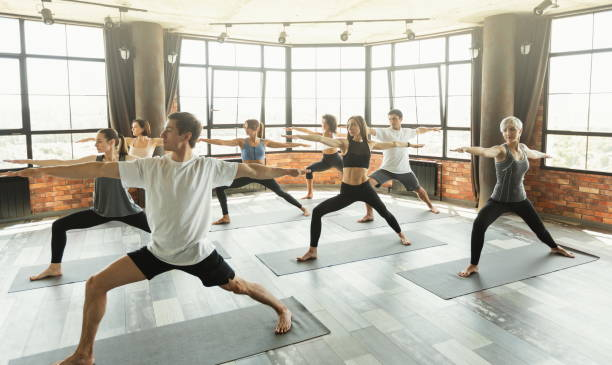 Millennials practicing yoga in a modern studio Group of young sporty people practicing yoga, standing in Warrior two pose, Virabhadrasana II pose, yogi millennials in a modern studio. yoga class stock pictures, royalty-free photos & images