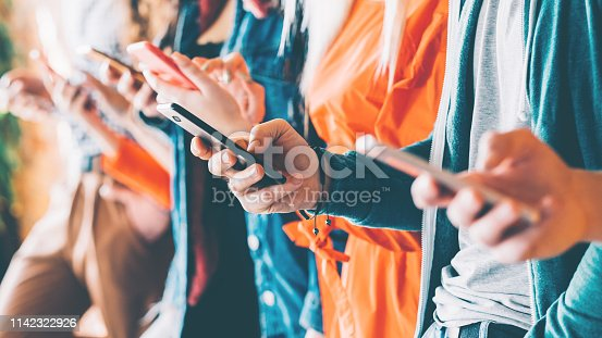 Millennials in digital age. Cropped closeup of smartphones in young people hands. Youth addicted to social networking services.