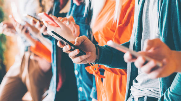 millennials social networking services addiction Millennials in digital age. Cropped closeup of smartphones in young people hands. Youth addicted to social networking services. ancestry stock pictures, royalty-free photos & images
