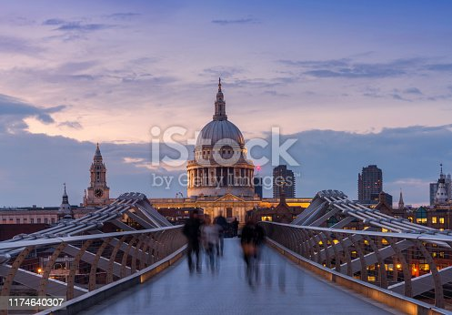 Millennium Bridge and St. Paul's cathedral with commuters at dusk