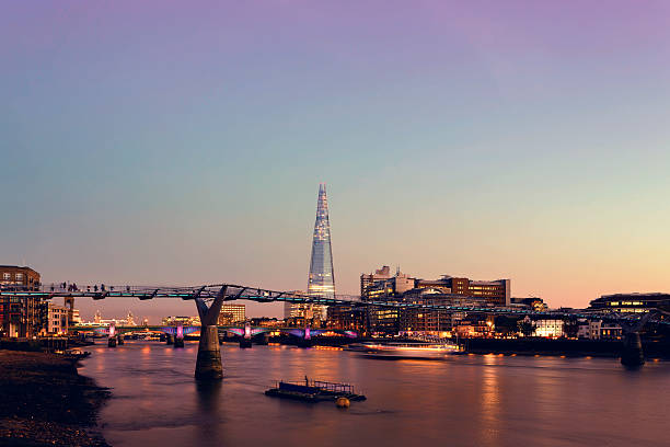 Millennium Bridge and The Shard in London at twilight View of Millennium Bridge, The Shard, Southwark Bridge and Tower Bridge in a pink twilight railway bridge stock pictures, royalty-free photos & images