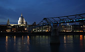 A night panorama stock image of the London Millennium Footbridge and the illuminated St Paul's Cathedral dome