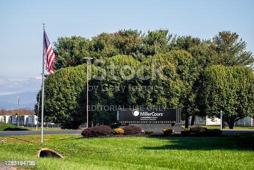 Elkton, USA - October 27, 2020: Millercoors brewery manufacturing brewing company plant factory, beer facility sign with American flag in rural countryside Rockingham county